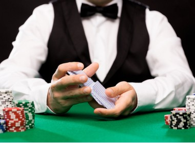 dealer sitting at a poker table with cards and chips in front of him