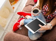 woman relaxing on her sofa with her tablet and a cup of coffee
