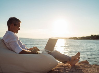 man relaxing with his laptop at the beach