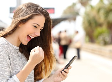 happy woman winning while playing online casino games on her phone
