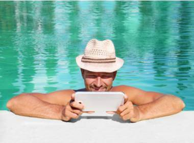 guy with a hat in the pool playing at Springbok Casino on his tablet