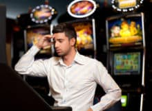 man in a land-based casino looking confused and disappointed