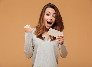 woman happily winning at Slotocash at Slots Play Casinos