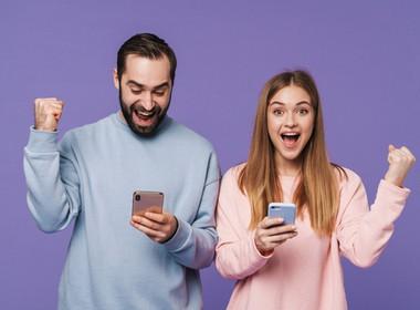 pria dan wanita masing-masing memenangkan permainan Grande Vegas di ponsel mereka